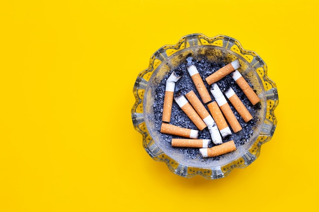 Smoked cigarettes on yellow background.