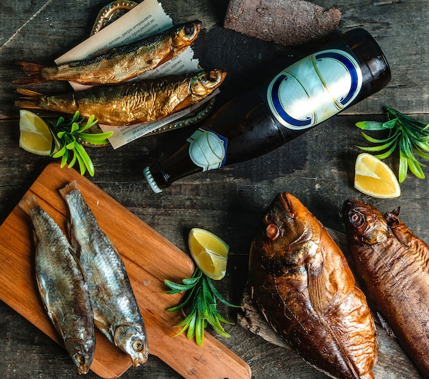 Smoked fish cold beer bottle and sliced lemon