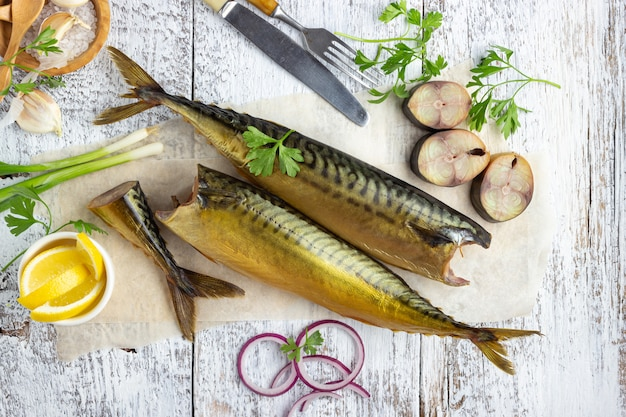 Smoked fish mackerel or scomber on a white wooden background. top view.