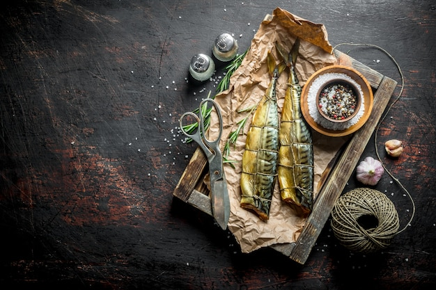 Smoked fish mackerel on a tray with twine, scissors and spices. on dark rustic background