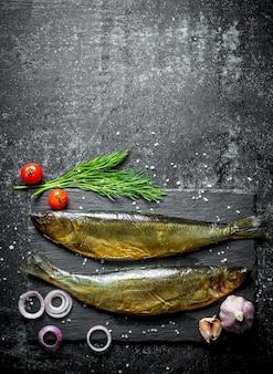 ディル、トマト、ニンニク、玉ねぎを添えた石板の魚の燻製。暗い素朴なテーブルの上
