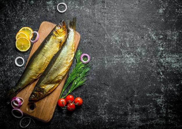 トマト、ディル、レモンスライスを添えた木製のまな板で魚の燻製。暗い素朴なテーブルの上