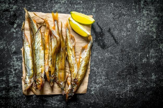 Копченая рыба на бумаге с ломтиками лайма на темном деревенском столе.