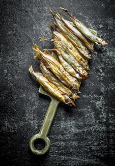 Копченая рыба на разделочной доске. на темном деревенском