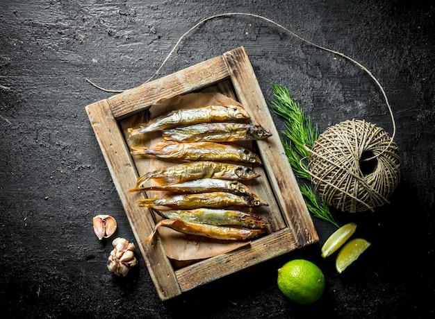 Копченая рыба на подносе с лаймом, шпагатом и чесноком. на черном деревенском столе
