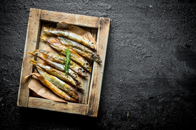 Копченая рыба на деревянном подносе на деревенском столе