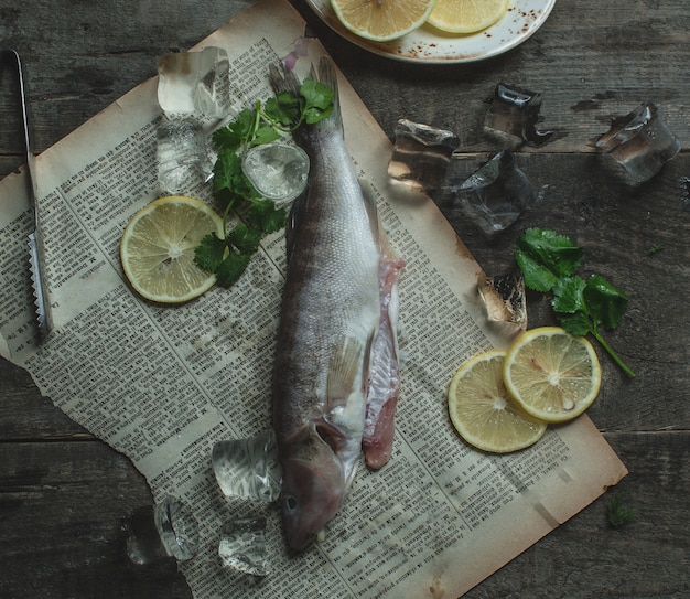 Smoked fish on a paper with lemon slices and basilic