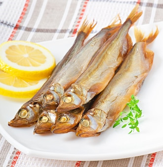 Smoked fish with lemon in a white plate