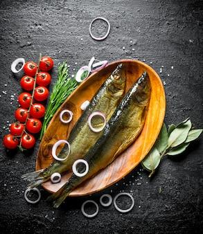 トマト、ディル、オニオンリングを添えた魚の燻製。黒い素朴なテーブルの上