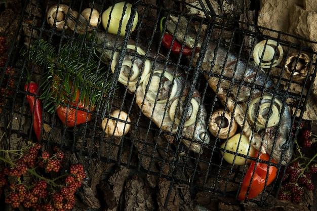 나무 껍질 배경에 야채와 소나무 가지를 곁들인 훈제 생선
