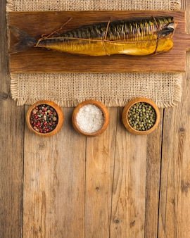 Smoked fish on wooden background