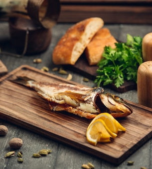 Smoked fish on a wooden board with a slice of lemon