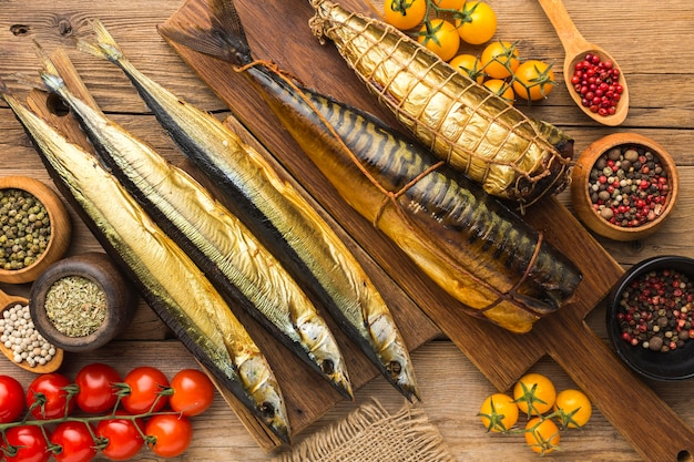 Smoked fishes on wooden table flat lay