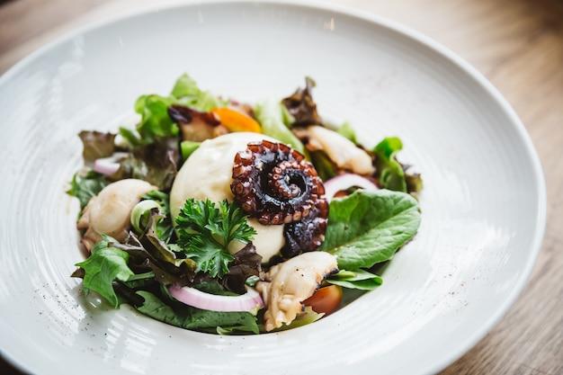 Smoked galician octopus with burrata cheese, radish, green oak and tomato.