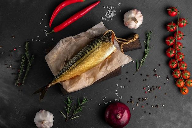 Копченая золотая форель с овощами на черной поверхности, вид сверху, концепция рыбного рынка