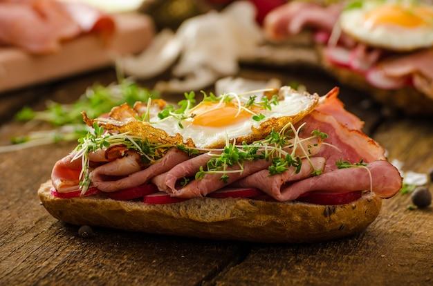 Сэндвич с копченой ветчиной на деревянном столе