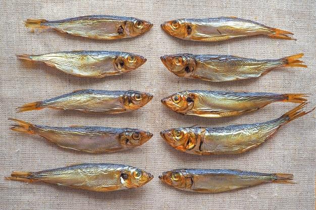 Копченая сельдь рыба. вкусная копченая рыба на мешковине.
