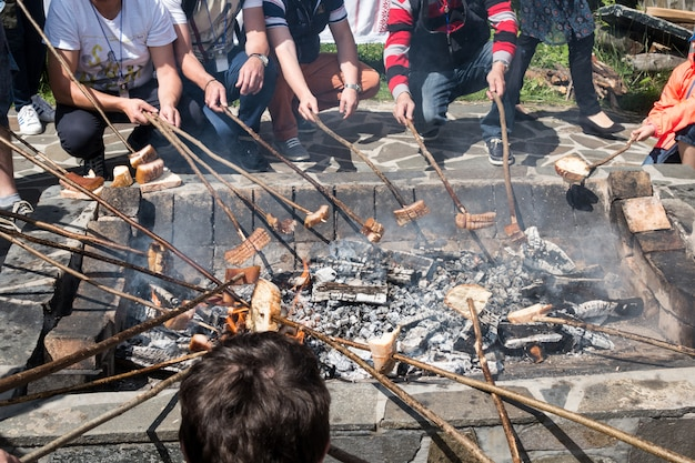 Smoked lard (slanina), sausages and bread cooked on fire.
