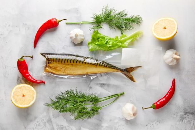 Копченая скумбрия, вокруг которой овощи, укроп, салат, лимон, перец, чеснок, на белом