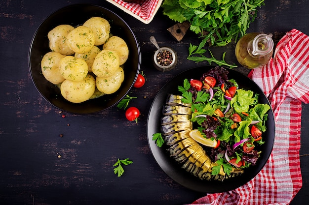 Smoked mackerel, boiled potatoes and fresh salad on dark background
