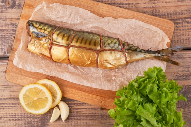 Smoked mackerel fish with lemon and greens on wooden board top view close up