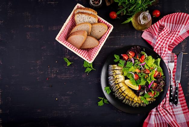 Smoked mackerel and fresh salad on dark background