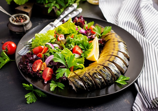 Smoked mackerel and fresh salad on a dark background.