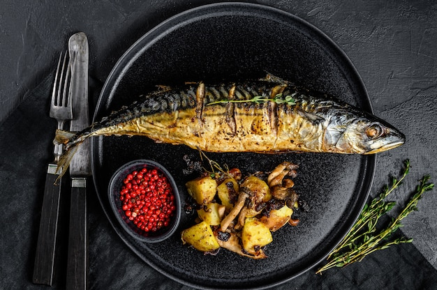 Smoked mackerel with fried potatoes and mushrooms. black background. top view