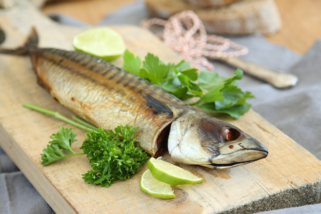 Smoked mackerel with lime and parsley on wooden board