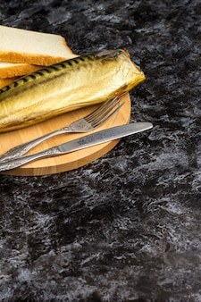 Smoked mackerel without head on cutting board