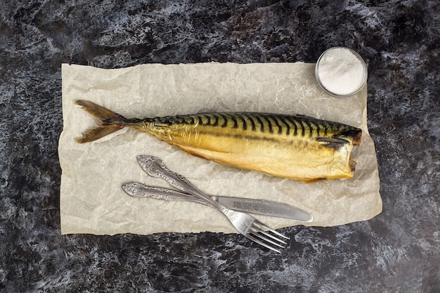 Smoked mackerel without head with fork knife on baking paper