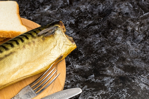 Smoked mackerel without head with fork knife cutting board bread. copyspace top view