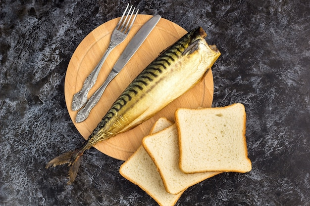 Smoked mackerel without head with fork knife cutting board bread