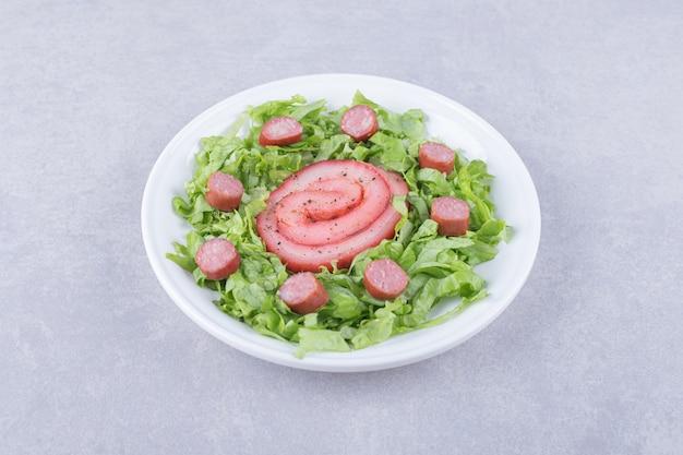 훈제 고기 롤과 하얀 접시에 슬라이스 소시지.