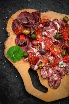Smoked meat, sausages, parma, jamon on a wooden board and a dark concrete table