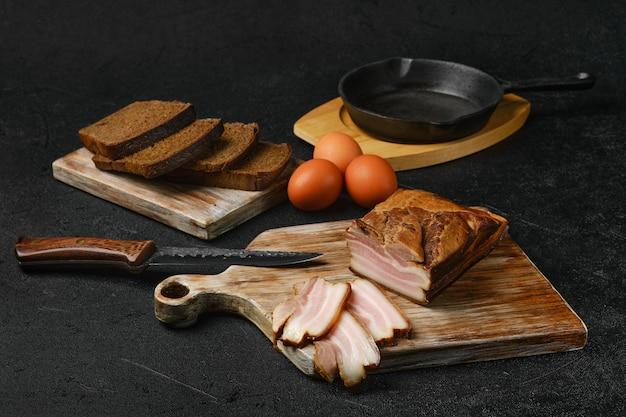 나무 도마에 갈색 빵과 계란을 곁들인 훈제 돼지고기 베이컨