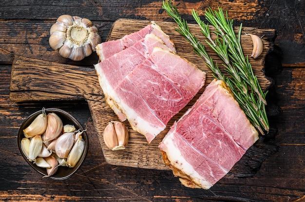 나무 소박한 커팅 보드에 훈제 돼지 고기 훈제 고기 조각. 어두운 나무 배경입니다. 평면도.
