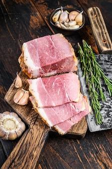 Кусочки копченого мяса окорока на деревянной разделочной доске в деревенском стиле