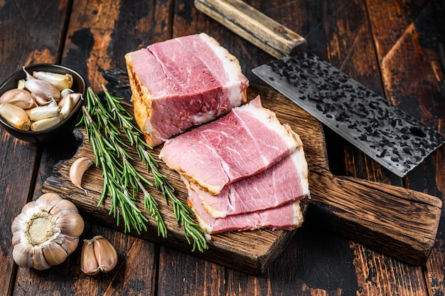 Smoked pork gammon meat slices on a wooden rustic cutting board