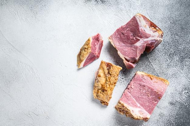 커팅 보드에 돼지 고기 목 고기를 훈제. 흰색 배경. 평면도. 공간을 복사하십시오.
