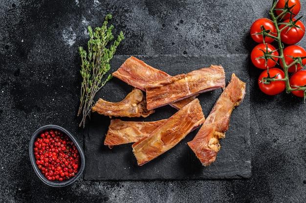 豚カルビの燻製。バーベキュースパイシースペアリブ。バーベキュー料理。黒の背景。上面図。