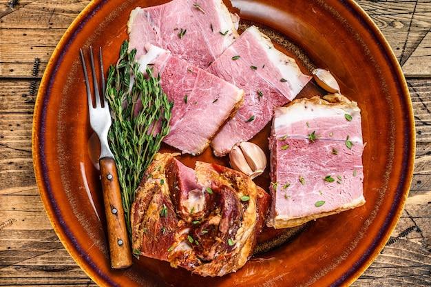 Копченая свинина slab ломтики мяса бекона на деревенской тарелке.