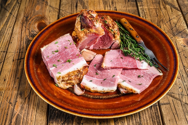Smoked pork slab bacon meat slices on a rustic plate