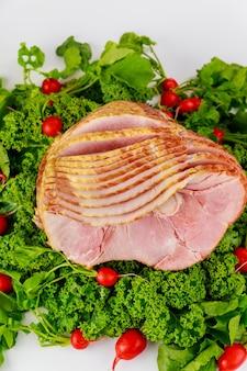 Smoked and presliced pork ham decorated with fresh radish.