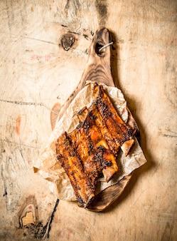 木製の背景に古いボードでグリルしたスモークリブ