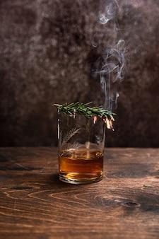 ウイスキーまたはバーボンのグラスにローズマリーを燻製