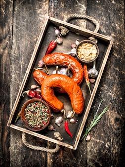 スパイスとニンニクのスモークサラミ。木製の背景に。