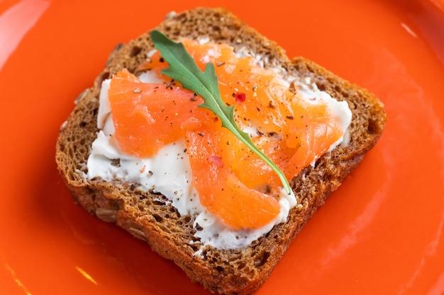 Сэндвич с копченым лососем и сыром филадельфия на ржаном хлебе со шпинатом из семян рукколы