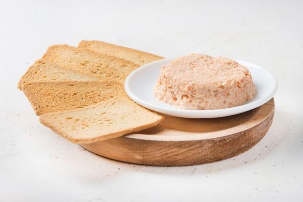 Паштет из копченого лосося и мягкого сыра с черным хлебом и морковью на белом