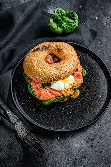 Smoked salmon bagel toasts with soft cheese, spinach and egg.